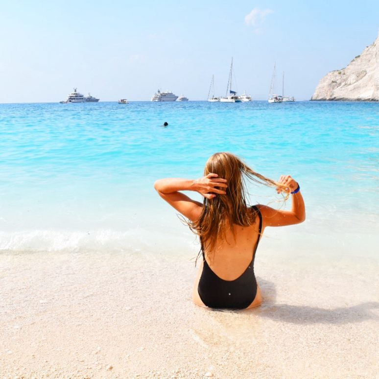 Woman sitting at Navagio Beach