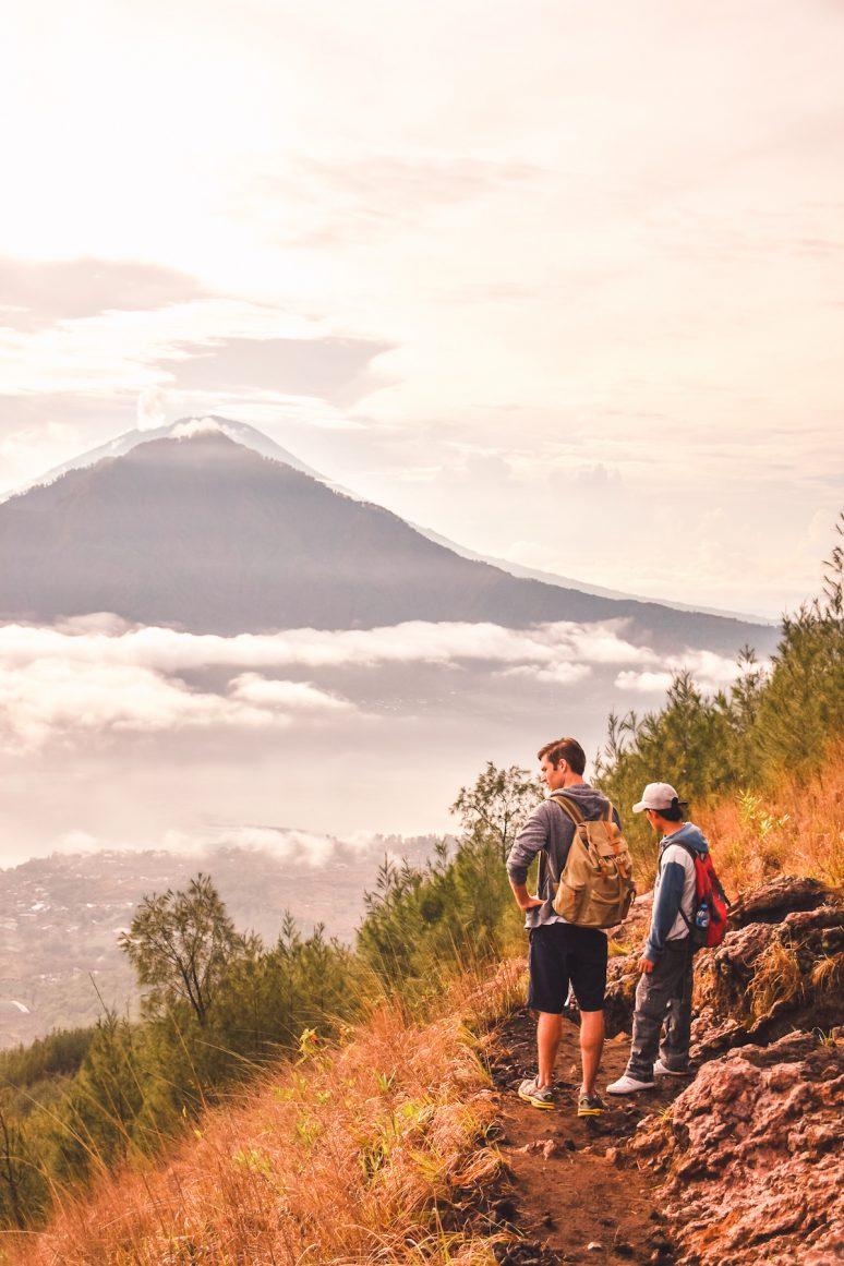 Two Men Hiking Mount Batur Sunrise Wearing Backpacks