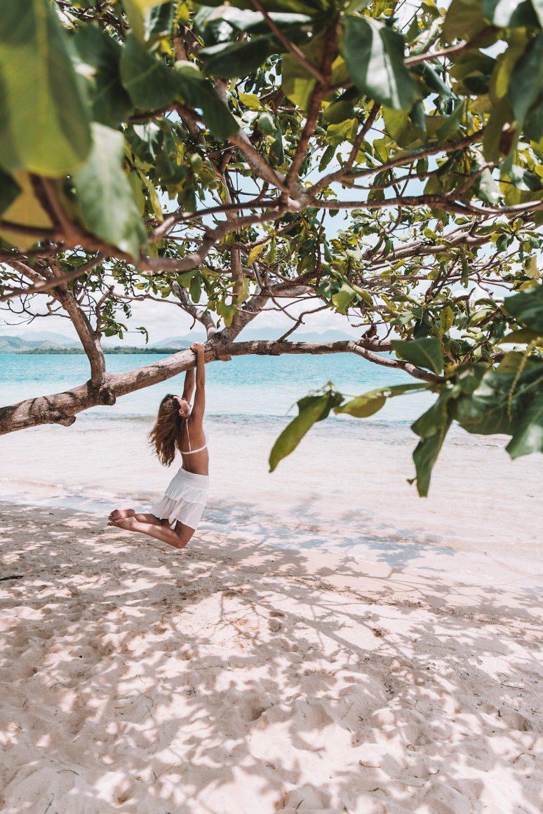 Woman swinging on tree on Cowrie Island in Honda Bay, Philippines