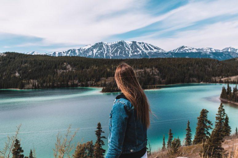 Woman looking at Emerald lake in Alaska