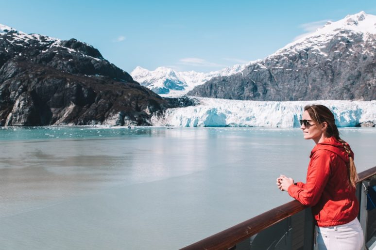 Woman on Alaska cruise with glacier in background