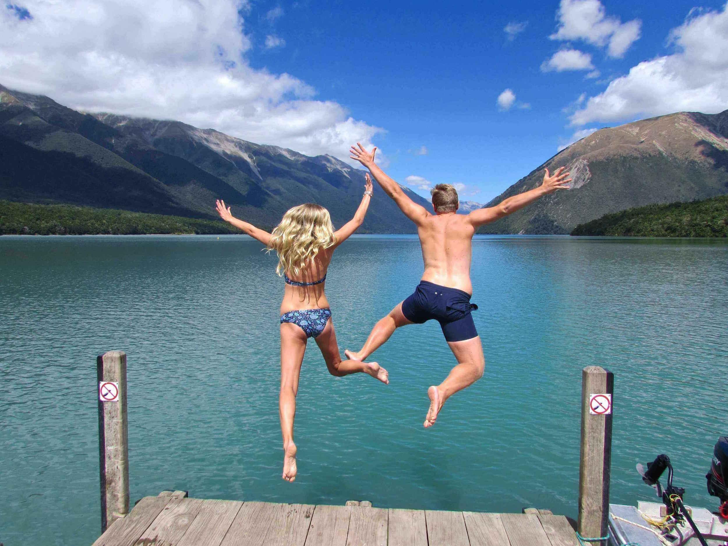 Couple jumping off jetty at Lake Rotoiti