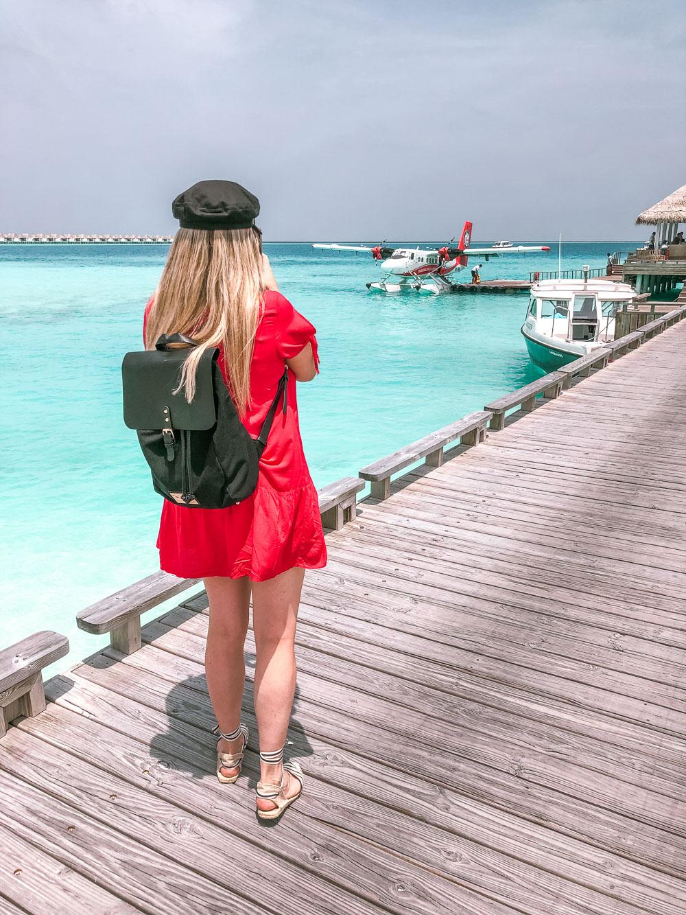 Woman on deck looking at sea plane on ocean
