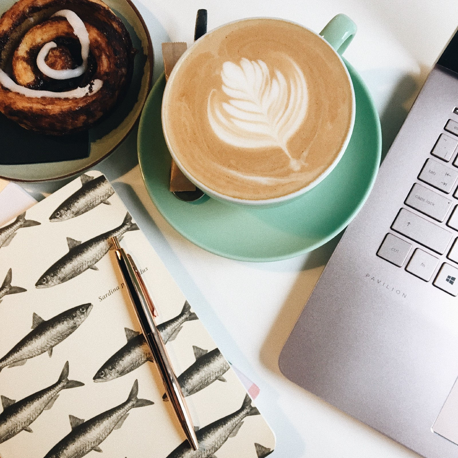 Coffee, cinnamon roll and laptop on table